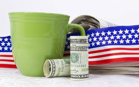 american currency: American currency placed in front of newspaper, flag design ribbon, and green mug on white linen