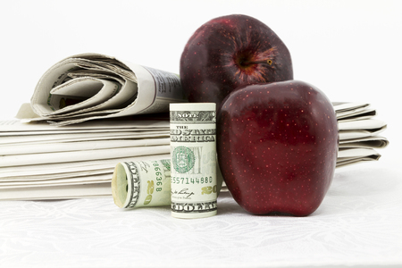 american currency: Two apples and American currency placed with stack of newspapers reflect news and information on education bonds and finances.