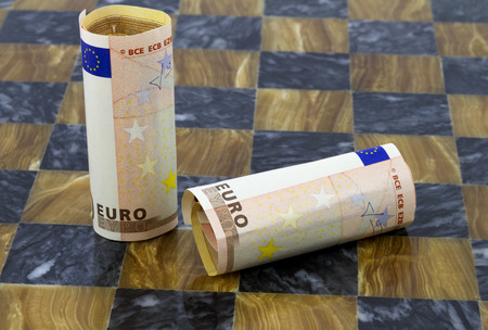 instability: Two euro bills with one fallen on chess board reflect instability of currency market and European Union countries.  Weak, unbalanced financial condition and lack of confidence symbolized.