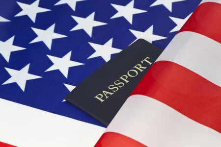citizenship: Stars and stripes of American flag are placed behind a passport reflecting pride in citizenship and travel.