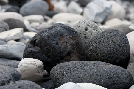 igneous: Beautiful and natural black volcanic rocks on beach of Hellnar, a tiny town on the westernmost part of Icelands Snaefellsnes peninsula.  Many stones display the bubbly appearance and coarse grained texture of igneous rock.
