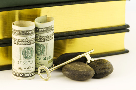 attainment: American currency with books, key, and rocks symbolizes the strategic investment goal of money for education and its difficult attainment in rocky times. Stock Photo