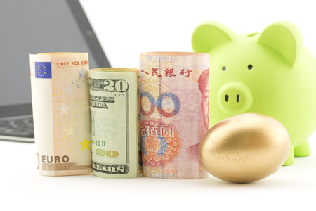 global retirement: Three currencies, euro, dollar, and yen, placed with gold nest egg with computer and bank in background reflect strategic global investment and success. Stock Photo