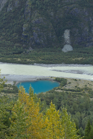shrinking: Unique blue of glacial pool at toe of Salmon Glacier reflects the melt of climate change on 5th largest glacier in North America.  Location is north of Hyder, Alaska, USA, and Stewart, British Columbia on Canadian side of border.  Date taken is September, Stock Photo