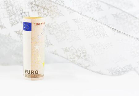 shifting: Euro currency on swirl of white snowflake ribbon background reflects shifting financial environment
