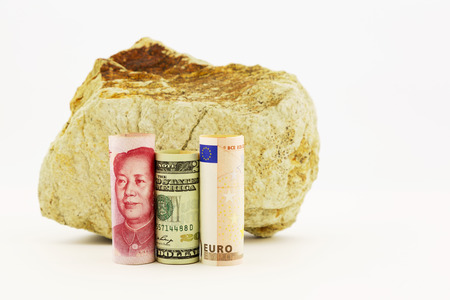 influential: Influential currencies, the Chinese yuan, American dollar, and European Union euro, placed next to rock reflect rocky, worldwide financial times. Stock Photo