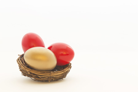 volatility: Two red eggs and one gold egg in nest reflect important choices in business and investing. Copy space on white background.