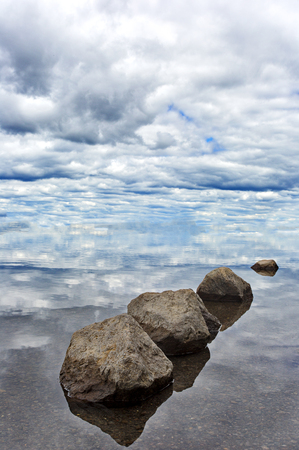 destination scenics: Serene balance of rocks leads gaze to the sky and clouds.  Location is Lewis Lake in Yellowstone National Park in Wyoming.