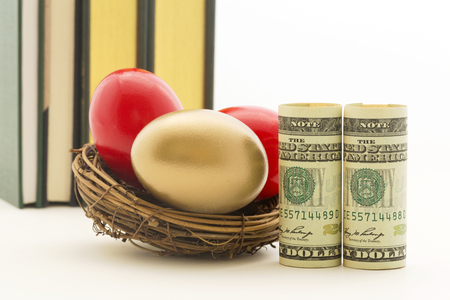 financial diversification: Pair of red nest eggs and two, symbolic American dollars reflect risks and dangers in business and investments.  Gold nest egg shows benefit of diversified portfolio. Stock Photo
