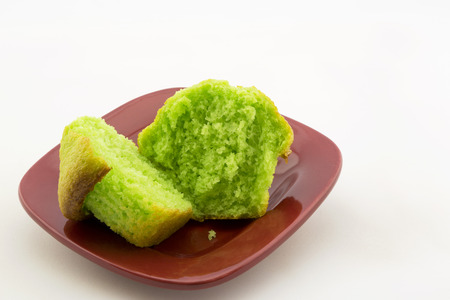 Vibrant green of sliced, fresh pistachio nut muffin.  Specialty baked good on red plate.  Copy space above on horizontal image.