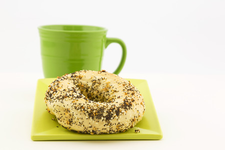 Bagel and coffee presentation with garlic, sesame and poppy seeds as topping and green mug adjacent.  Still life in horizontal image with copy space. Crumbs on plate.