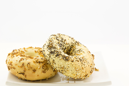 Everything bagel propped against onion bagel on white plate.  Specialty toppings are sesame and poppy seeds, roasted onion and garlic bits.  Horizontal image with copy space.