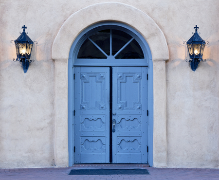 Morning rays begin to illuminate the azure blue, double doors of San Felipe de Neri church in Old Town, Albuquerque, New Mexico. Iron lanterns still glow on adobe wall. This historic church building is listed on National Register of Historic Places.  Pres