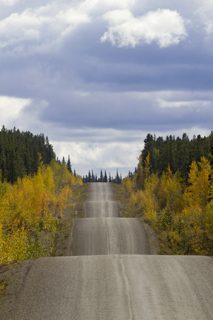 Autumn along the adventurous rise and fall of Cassiar-Stewart Highway in British Columbia. Vertical photograph with copy space in sky. Rambling road travel symbol.  Date is September 6, 2015. Stock Photo