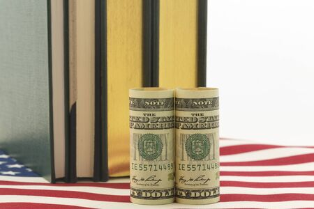 governmental: American currency in front of books on stars and stripes pattern. Symbols reflect issues of cost, investment needs, and governmental policy related to education.