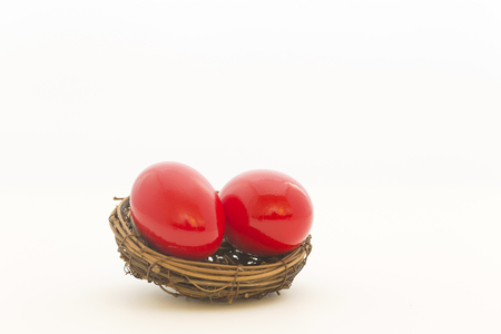 Two, crimson red nest eggs are symbols of endangered investments, pensions at risk, heavy debt, and repercussions upon a fragile economy.