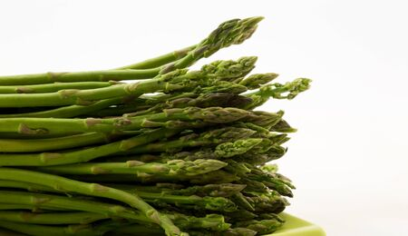 Fresh asparagus spears laid lengthwise on green plate against white background with copy space on right of horizontal photograph.