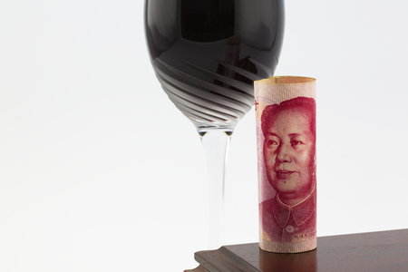 profit celebration: Chinese yuan money with celebratory red wine in stem glass on polished wood box.  Horizontal photograph with copy space.