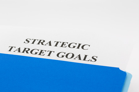 Blue file folder with Strategic Target Goals report cover slipped out.  Horizontal photograph with copy space.