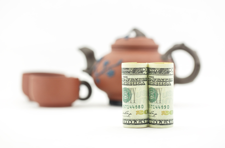 Taking time for tea and business decision.  American dollar currency with tea pot and two cups in background. Conceptual symbols for reflection and collaboration add to financial metaphor. Stock Photo