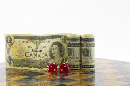 Red dice, game board, Canadian dollar, and American dollar reflect risk and opportunities in economic diplomacy.