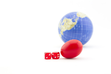 Dice and red nest egg with global background signify financial gamble and risks inherent in business, investment, and personal finance decisions.