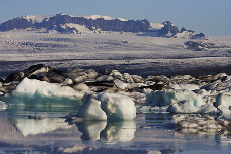 Scenic view of mountains, snow, and the changing scene of floating icebergs in Jokulsarlong Glacier Lagoon in East Iceland.  Stock Photo