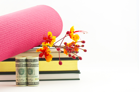 industry trends: Commitment and dedication bring growing success in fitness industry trends reflected in books, yoga mat, flowers, and American currency on white background with copy space.  Stock Photo