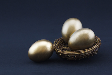 Black background adds drama to success concept of three, gleaming gold nest eggs.  Copy space available on horizontal photograph.