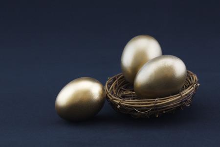 Lo sfondo nero aggiunge drammaticità al concetto di successo di tre splendenti uova d'oro. Copia spazio disponibile sulla fotografia orizzontale. Archivio Fotografico - 80149285