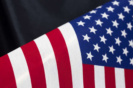 Stars and stripes American flag pattern against simple, black satin. Horizontal photograph with copy space.  Background suggests memorial, patriotism, courage, and faith.