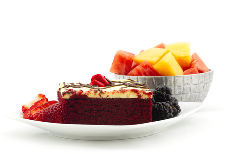 Square cut of iced red velvet cake with berries and metal bowl filled with cubes of watermelon and cantaloupe.  Summer dessert in horizontal image with copy space. Stock Photo
