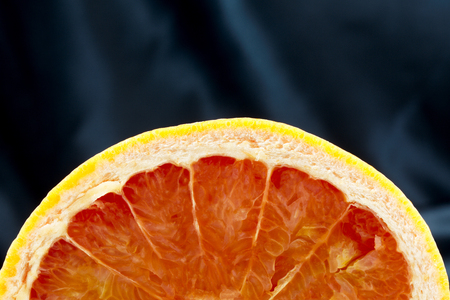 Background with copy space macro photograph of sliced, half grapefruit like a juicy fruit half moon with black satin behind.