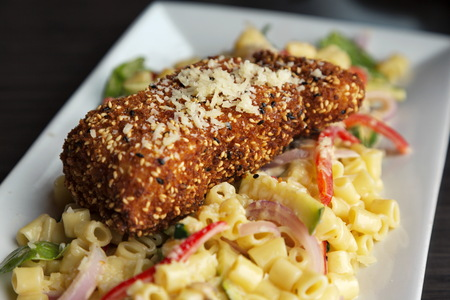 Fresh halibut seafood is tempting with sesame seed crust and noodle salad on contemporary, rectangular, white platter Stock Photo