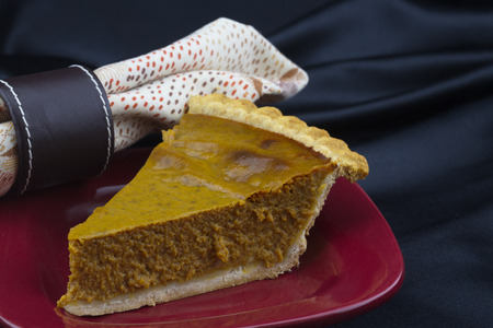 Delicious slice of moist pumpkin pie with tender pastry crust on red plate Stock Photo