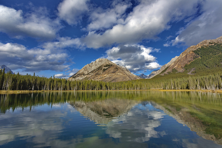 Big blue sky, mountains, and beautiful clouds reflect in still waters of Buller Pond in Spray Valley Provincial Park in Alberta, Canada.  Horizontal landscape with copy space.