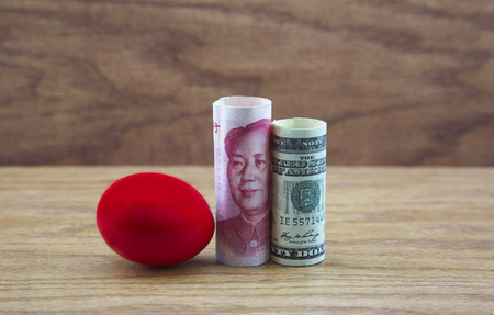 Crimson nest egg placed with Chinese and American currency reflects a risky investment environment.