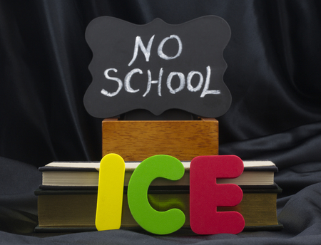 ICE in letters with NO SCHOOL on small chalkboard with books and black satin background. Icy weather conditions create danger and school closings. Reklamní fotografie