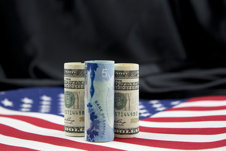 Economic policy conflicts and pressures between nations reflected by Canadian dollar wedged between American dollars placed on flag with black satin background
