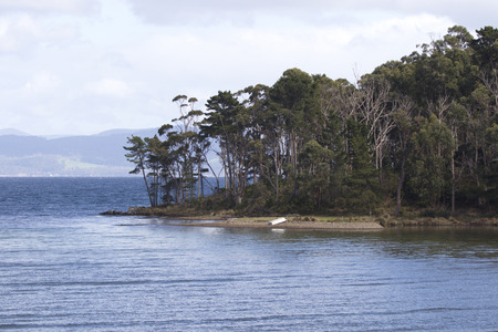 Small row boat rests overturned on beautiful isolated shore of Daniels Bay on Bruny Island in Tasmania