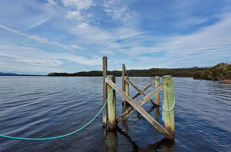 Connection visible in worn beauty of  wood pilings with connecting, fresh blue rope at Sarah Island near Strahan in Tasmania in Australia. Reklamní fotografie