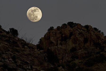 Full moon over rugged mountain ridges of Mt. Lemmon along Catalina Highway in Arizona