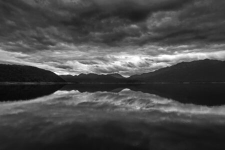 Black and white reflects the gray cloudiness of weather blowing onto Lake Burbury in Tasmania Фото со стока