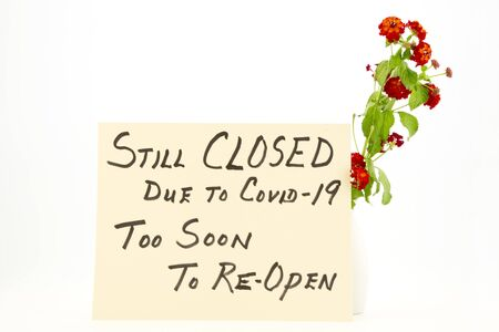 Bright red and orange lantana flowers accent a handwritten Too Soon to Reopen Covid 19 Sign