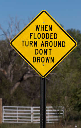 Sign for Flash Flooding indicates WHEN FLOODED TURN AROUND DON'T DROWN