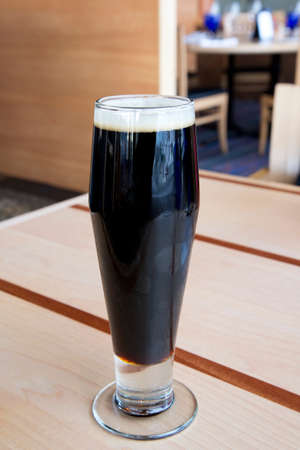 Dark beer with foam on top in tall glass on table looks cold and tempting Stock Photo