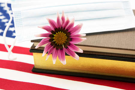 Accent on science for national medical and pandemic guidelines emphasized by flower with Covid Mask and science books on American flag Stock fotó