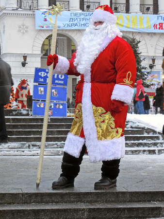 russian santa claus (Father Christmas) with magical wand in national red suite at the street before new year holiday in Kiev, Ukraine.