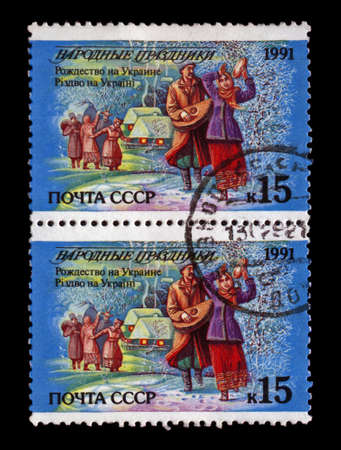 USSR - CIRCA 1991: cancelled stamp printed in the USSR, shows ukranian people dancing during Christmas holiday, tree under snow and small houses at night, circa 1991. Christmas in Ukraine as text. Stock Photo