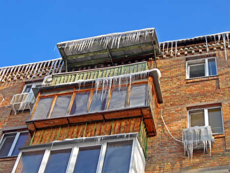 winter icicles heap on the roof of building, seasonal stress details photo